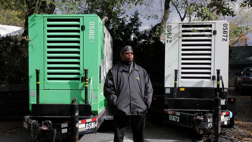 A security guard stands by two power generators adjacent to the New York City Marathon facility in New York's Central Park, Friday, Nov. 2, 2012. (AP / Richard Drew)