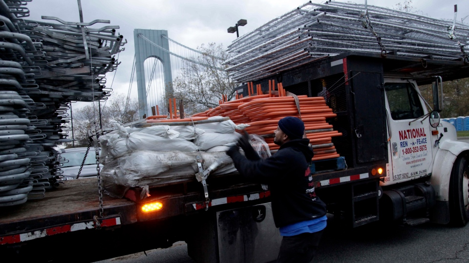 Pedro Cabrera, who was working at the starting line, stops setting up fence and secures his company's gear after the cancellation of the New York City Marathon in Staten Island, New York, Friday, Nov. 2, 2012. (AP / Seth Wenig)