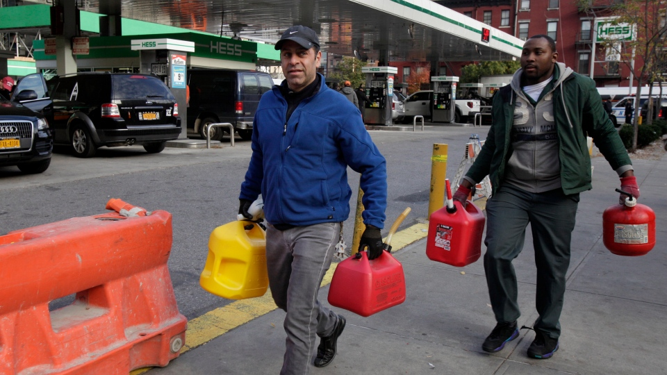 Two men carry filled containers of gasoline as they leave a gas station, in New York on Friday, Nov. 2, 2012. (AP /Richard Drew)