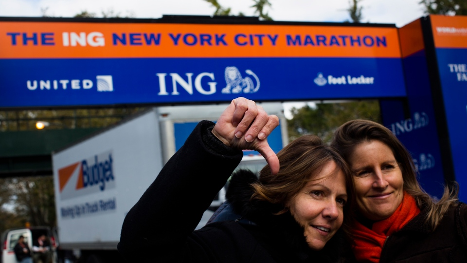 Celine Bally, 42, of French Martinique, gives a thumbs-down in front of the Central Park finish line for the now canceled New York Marathon,  in New York, Saturday, Nov. 3, 2012. (AP / John Minchillo)