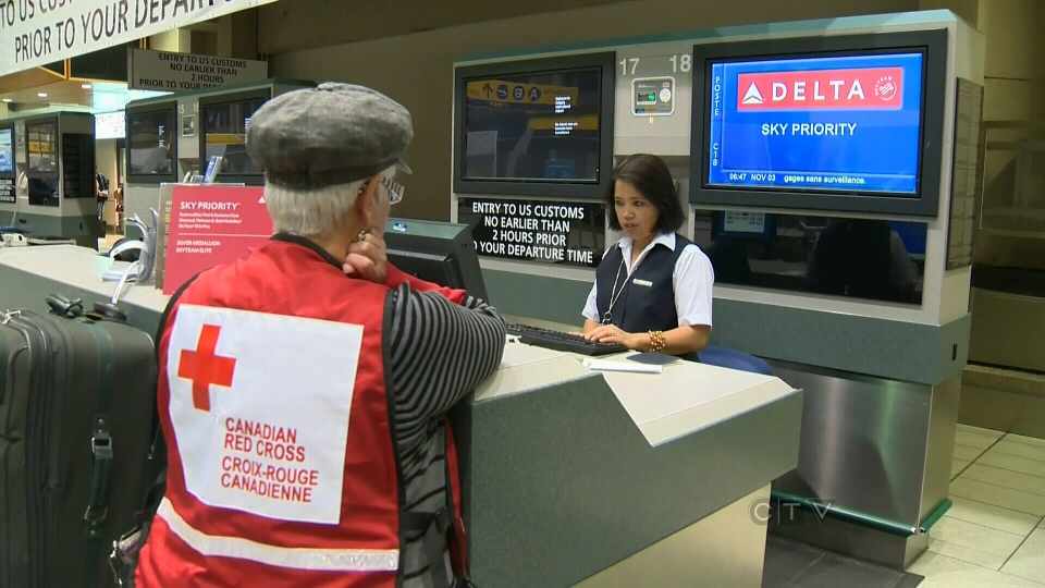 Canadian Red Cross volunteer Susan MacKenzie purchases a ticket to New York in the Calgary airport, Saturday, Nov. 3, 2012.