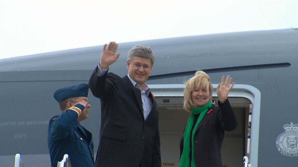 Stephen Harper and his wife Laureen wave to the media before boarding a plane en route for India, at the Ottawa airport, Saturday, Nov. 3, 2012.