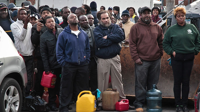 A crowd gather at a service station with portable containers, waiting for gas pumps to open, in the Brooklyn borough of New York on Saturday, Nov. 3, 2012. (AP /Bebeto Matthews)