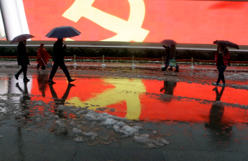 Residents walk past an image of the Chinese Communist Party flag displayed on a giant screen on Tiananmen Square in Beijing, China, Sunday, Nov. 4, 2012. (AP / Ng Han Guan)