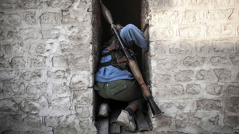 A rebel fighter takes cover as he looks back up at a warplane attacking rebel positions during heavy clashes between rebel fighters and the Syrian army on Saturday, Nov. 03, 2012. (AP / Narciso Contreras)