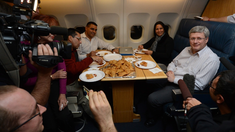 Prime Minister Stephen Harper shares a plate of samosas with reporters and colleges while en route to India from Ottawa on Saturday, Nov. 3, 2012. (Sean Kilpatrick / The Canadian Press)