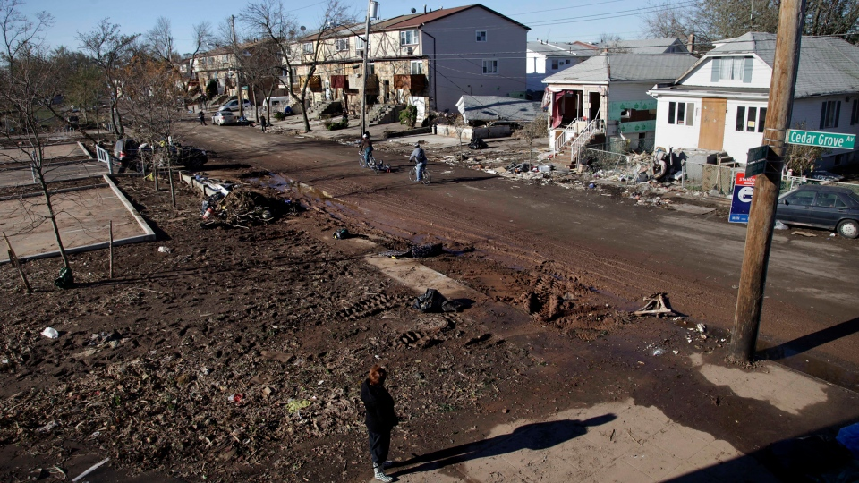 Maryann Eger, bottom, looks over the destruction in her neighborhood of New Dorp in the Staten Island borough of New York, Sunday, Nov. 4, 2012, in the aftermath of Superstorm Sandy. (AP / Seth Wenig)