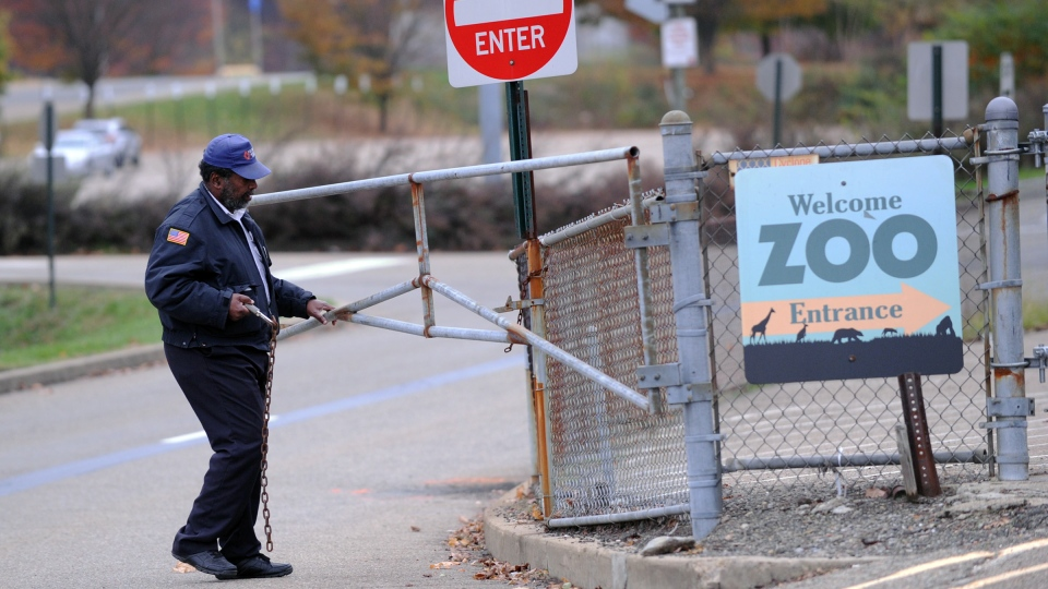 A security guard closes the gate at the Pittsburgh Zoo, where zoo officials say a young boy was killed after he fell into the exhibit that was home to a pack of African painted dogs, who pounced on the boy and mauled him, Sunday, Nov. 4, 2012. (AP / John Heller)