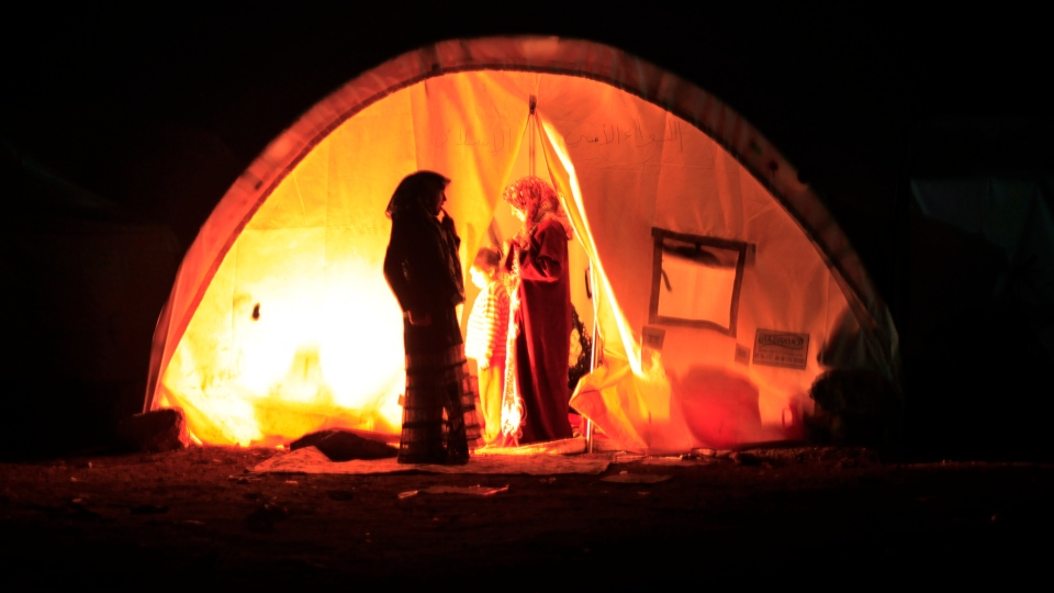 A Syrian family who fled the violence in their village, set up a fire inside their tent at a camp in the Syrian village of Atma, near the Turkish border with Syria, Sunday, Nov. 4, 2012.(AP / Khalil Hamra)