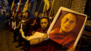 An exile Tibetan carries a portrait of the Tibetan spiritual leader the Dalai Lama during a candlelit vigil in Dharmsala, India, on Sunday, Nov. 4, 2012. (AP / Ashwini Bhatia)