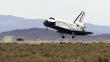 The landing gear has deployed as the space shuttle Discovery lands at Edwards Air Force Base, Calif., and the NASA Dryden Flight Research Center, Friday, Sept. 11, 2009. (AP Photo/Reed Saxon)