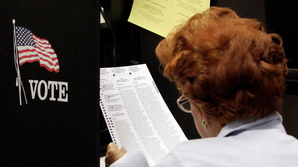 A voter reads her ballot as she prepares to cast her vote during the last day of early voting in Miami, on Saturday, Nov. 3, 2012. Despite record turnout in many parts of the state, Florida Gov. Rick Scott rejected calls to extend early voting through Sunday to help alleviate long lines at the polls. (AP / Alan Diaz)