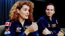 Canadian Space Agency astronaut Julie Payette explains her duties aboard space shuttle Discovery as Russian cosmonaut Valery Tokarev watches during a post flight press conference at Kennedy Space Station, Fla., Monday, June 7, 1999. (AP Photo/Peter Cosgrove)