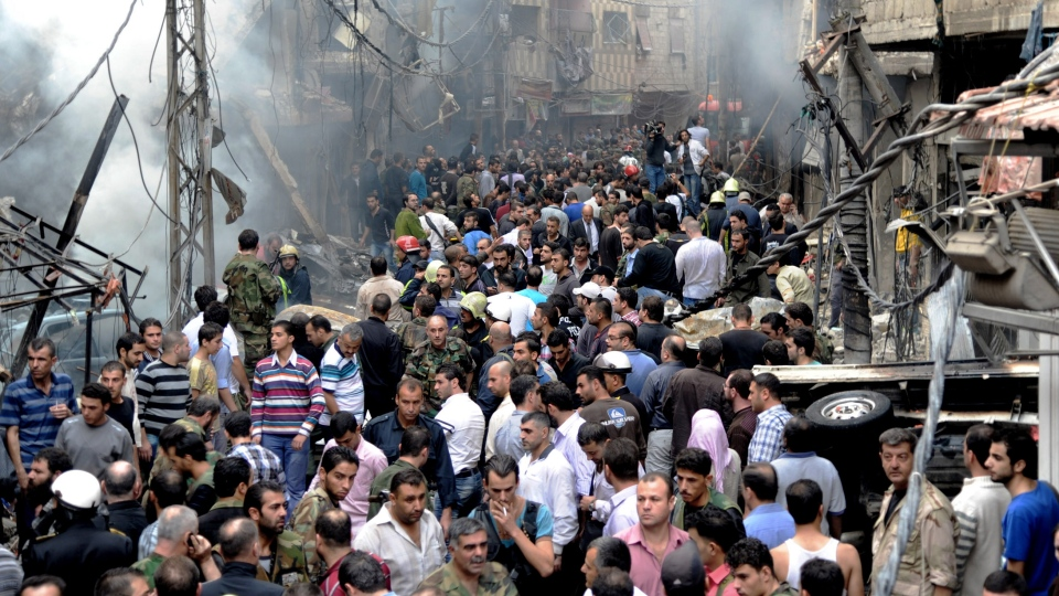 Syrians stand at the scene of a blast in the Mazzeh al-Jabal district of the Syrian capital Damascus, Syria, Monday, Nov. 5, 2012. (AP / SANA)