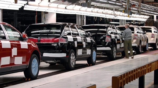 A worker inspects vehicles as they roll off the line at the assembly plant in Oakville, Ont. on Monday Oct. 16, 2006. (Aaron Harris / THE CANADIAN PRESS)