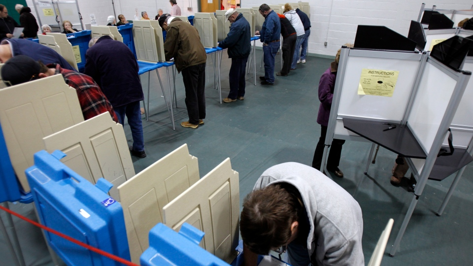 U.S. voters are seen at polling booths on Tuesday, Nov. 6, 2012 in Shelburne, Vt. (AP Photo/Toby Talbot)