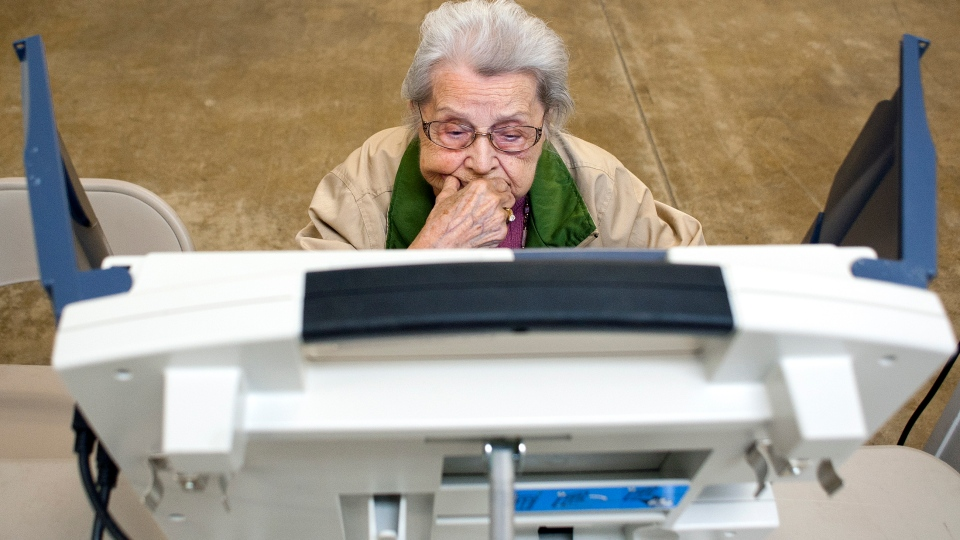 Alvina DeVault, who is 91 years old and hasn't missed casting her ballot in an election since Franklin D. Roosevelt was president, takes a moment to contemplate her choices while voting at the Tippecanoe County Fairgrounds, in Lafayette, Ind., on Tuesday, Nov. 6, 2012.  (The Journal and Courier / Brent Dinkut)