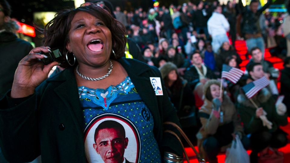 Martha Nunez, 53, of the Bronx, reacts to positive predictions for President Barack Obama as crowds watch election results in Times Square in New York, Tuesday, Nov. 6, 2012. (AP / John Minchillo)