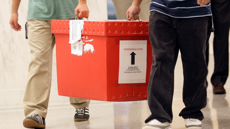 San Francisco Department of Elections workers carry a box of voted ballots from the mail at City Hall in San Francisco, Tuesday, Nov. 6, 2012.  (AP  /Jeff Chiu)