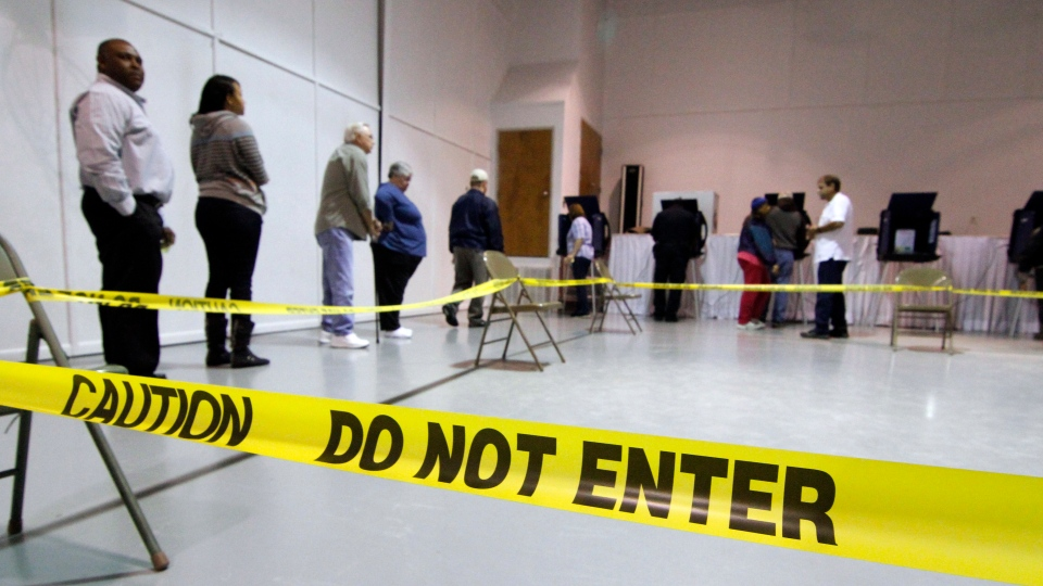 Voters wait their turn to vote at a electronic voting booth in this Pearl, Miss., precinct, Tuesday, Nov. 6, 2012.(AP / Rogelio V. Solis)