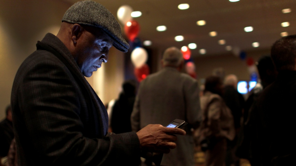 Virvus Jones keeps track of election results on a mobile device as he attends an election night watch party on Tuesday, Nov. 6, 2012, in St. Louis. (AP / Jeff Roberson)