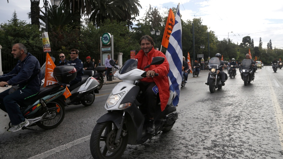 Local authorities workers riding their motorbikes as they protest in central Athens on Wednesday, Nov. 7, 2012.  (AP / Dimitri Messinis)