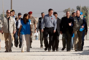 Britain's Prime Minister David Cameron, center, walks with Jordanian Foreign Minister Nasser Judeh, second left, and United Nations High Commissioner for Refugees (UNHCR) representative to Jordan Andrew Harper, right, during his visit to Zaatari refugee camp in Mafraq, Jordan, Wednesday, Nov. 7, 2012.  (AP Photo)