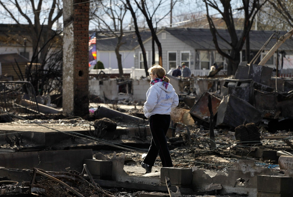 A woman walks through an area impacted by Superstorm Sandy in Breezy Point, NY, on Sunday, Nov. 4, 2012. (AP / Kathy Willens)