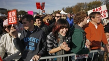 Sabrina de la Torre, center, laughs as footage from the Daily Show plays at the Rally to Restore Sanity and/or Fear in Washington, in Saturday, Oct. 30, 2010. (AP Photo / Jacquelyn Martin)