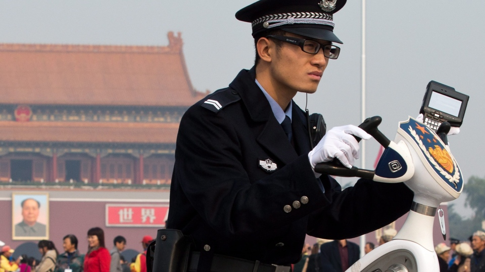 A policeman on a two-wheel electronic vehicle holds a scanner for checking identity cards watches a crowd at Tiananmen Square in Beijing on Friday, Nov. 2, 2012. (AP / Andy Wong)