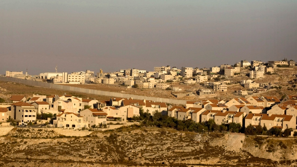 The Jewish neighborhood of Pisgat Zeev in east Jerusalem is seen with the Shuafat refugee camp, background, and Israel's separation barrier running between them, July 29, 2009. (AP / Sebastian Scheiner)
