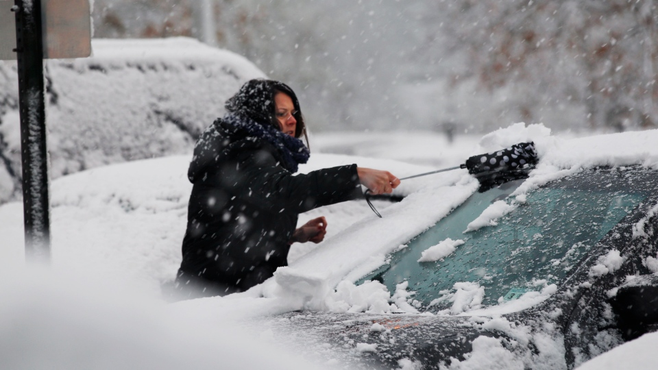 A woman clears snow from her parked car, in Dover Township, N.J., Wednesday, Nov. 7, 2012. (AP / Mel Evans)