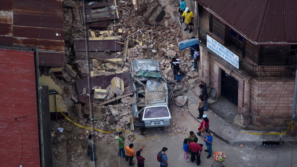 Residents walk among rubble after a magnitude 7.4 earthquake struck in San Marcos, Guatemala, Wednesday Nov. 7, 2012. (AP / Moises Castillo)