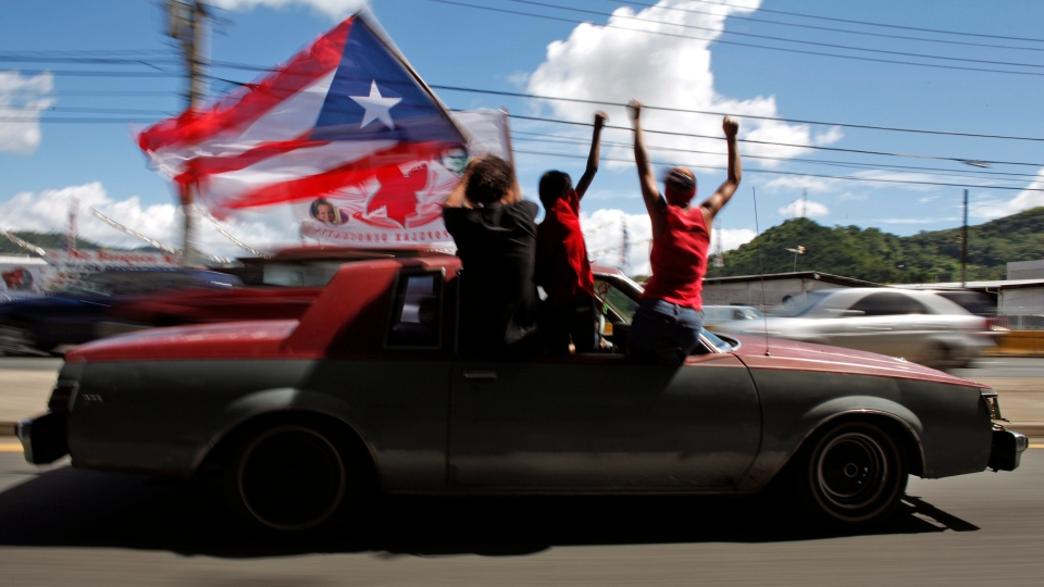 People ride atop a vehicle waving a Puerto Rican flag during elections in San Juan, Puerto Rico, Tuesday, Nov. 6, 2012. (AP / Ricardo Arduengo)