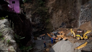 Residents and rescue workers use heavy equipment to look for people feared buried at a sand mine, after a magnitude 7.4 earthquake struck in San Marcos, Guatemala, Wednesday Nov. 7, 2012. (AP / Moises Castillo)