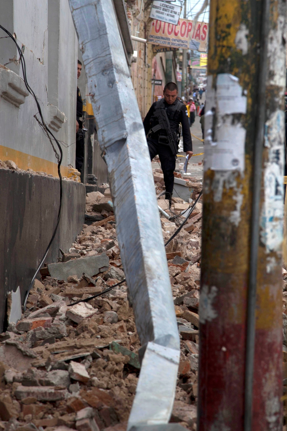 A police officer looks at rubble after a magnitude 7.4 earthquake struck in San Marcos, Guatemala, Wednesday, Nov. 7, 2012. (AP / Moises Castillo)