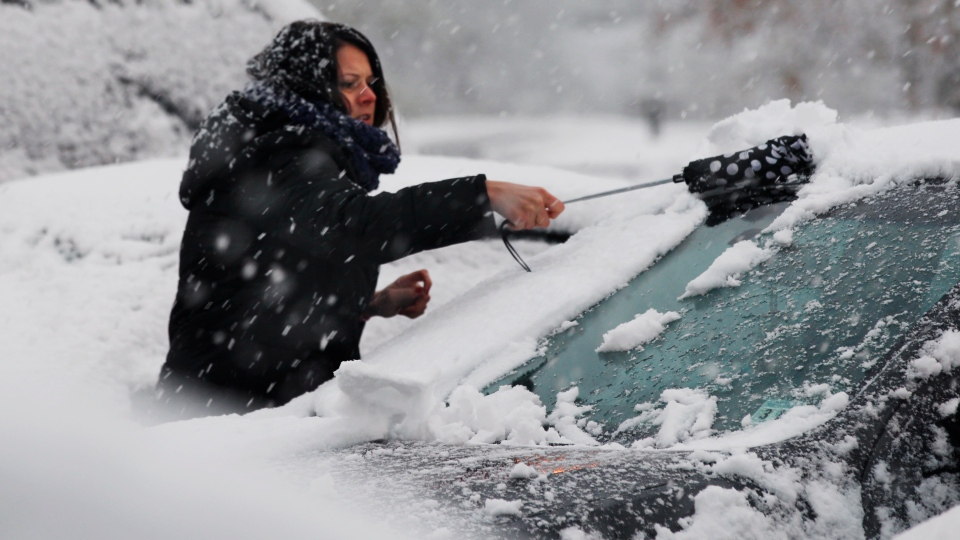 A woman clears snow from her parked car Wednesday, Nov. 7, 2012, in Dover Township, N.J., as the region pounded by superstorm Sandy last week is hit by a nor'easter. (AP / Mel Evans)