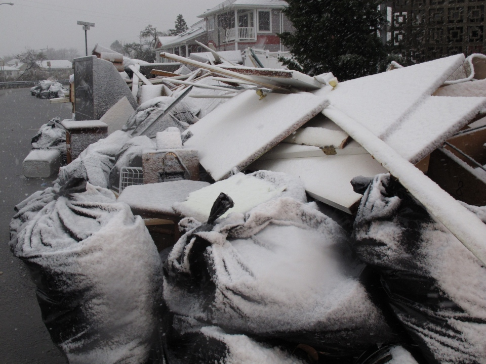 Snow covers debris piles as flood waters start to return to neighbourhoods in Point Pleasant Beach, N.J., Wednesday Nov. 7, 2012, as a nor'easter hits. (AP / Wayne Parry)