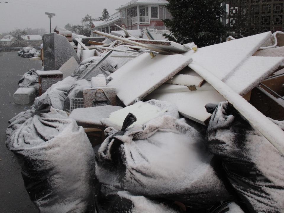 Snow covers debris piles as flood waters start to return to neighbourhoods in Point Pleasant Beach, N.J., Wednesday Nov. 7, 2012, as a nor'easter hits. (AP / Wayne Parry)