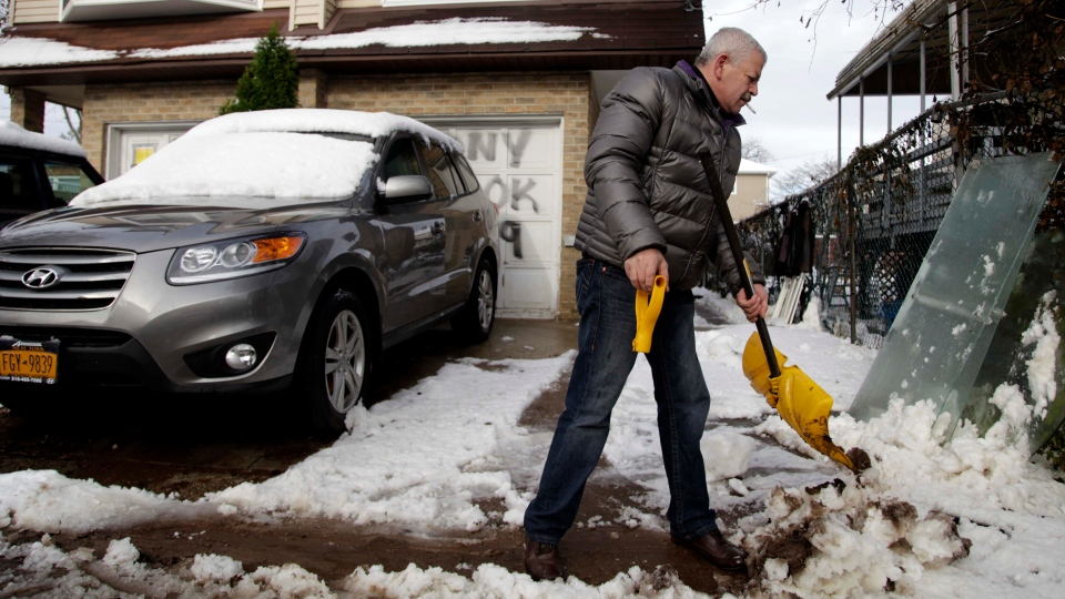 Gennady Naydis keeps clearing his driveway even as the handle breaks off his shovel in the New Dorp section of Staten Island, N.Y., Thursday, Nov. 8, 2012.  (AP / Seth Wenig)