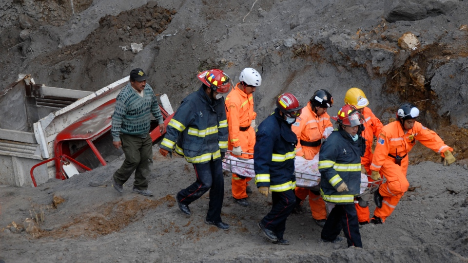 Rescue workers carry away the body of a person who was buried in a sand mine during an earthquake in San Marcos, Guatemala, Thursday, Nov. 8, 2012. (El Periodico de Guatemala, Alex Cruz)