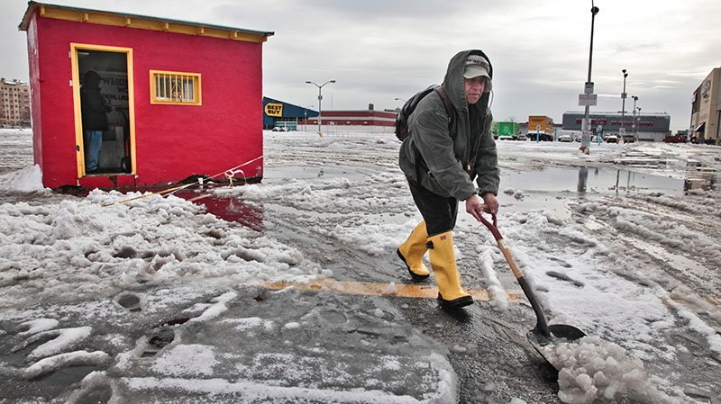 Gavino Hernandez shovels a path through the snow after arriving to survey damage to a one-room office building in Brooklyn, N.Y., Thursday, Nov. 8, 2012. (AP / Bebeto Matthews)