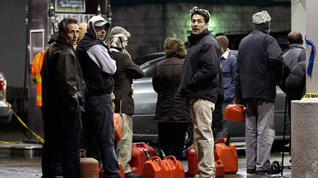 People line up with containers as they wait in line to get gas at a Hess station in the Brooklyn borough of New York where gas is still scarce, Thursday, Nov. 8, 2012.  (AP / Kathy Willens)