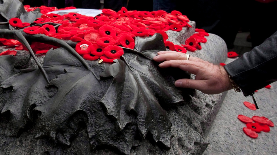 A man pauses as he touches the Tomb of the Unknown Soldier after placing his poppy on top following Remembrance Day ceremonies at the National War Memorial in Ottawa Friday November 11, 2011. (Adrian Wyld / THE CANADIAN PRESS)