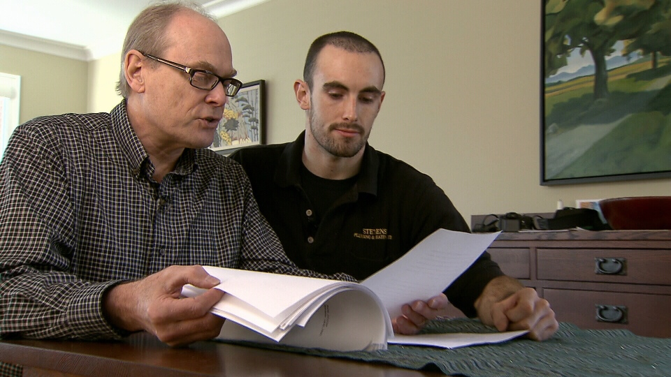 Jeffrey Moore, right, and his father Rick Moore look over a written decision from the Supreme Court of Canada, Friday November 9, 2012.