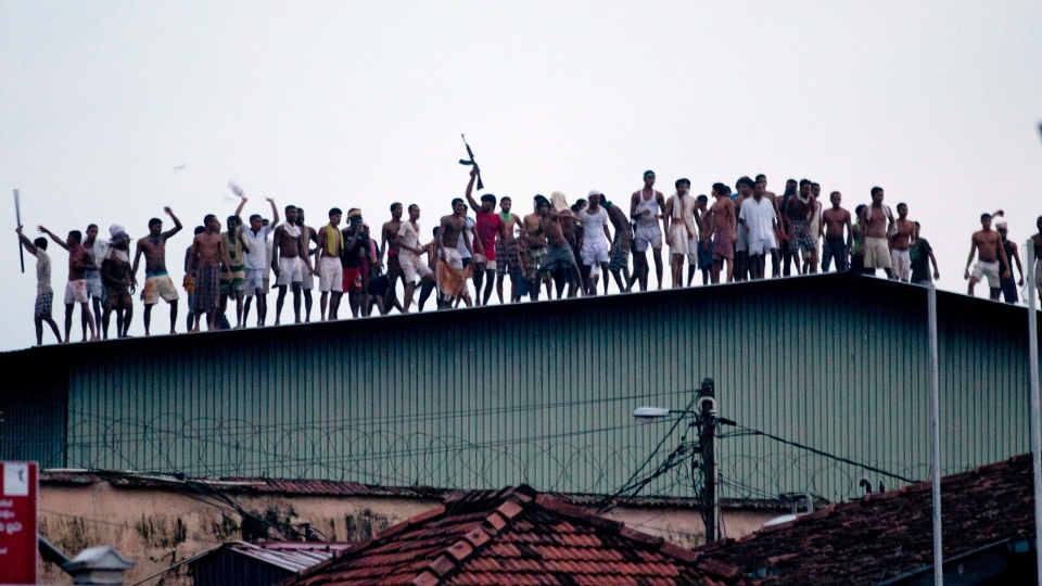 Sri Lankan inmates display guns, throw stones and shout slogans from a roof of a prison in Colombo, Sri Lanka, Friday, Nov. 9, 2012. (AP / Gemunu Amarasinghe)