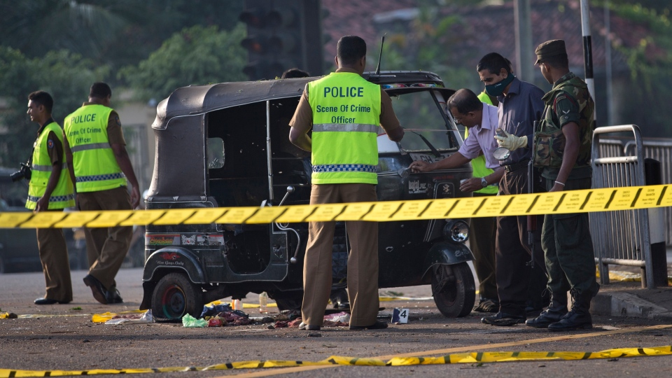 Police forensic officers examine a bullet-ridden three-wheeled vehicle used by inmates for their unsuccessful escape attempt, close to the entrance of a prison in Colombo, Sri Lanka on Saturday, Nov. 10, 2012. (AP / Gemunu Amarasinghe)