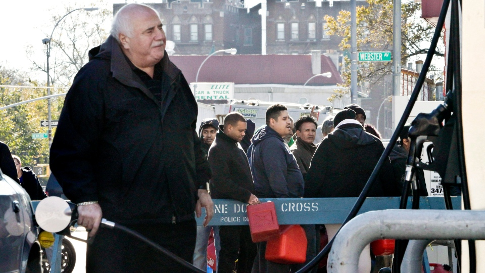 A motorist pumps gas while people stand in line with containers to purchase gas in Brooklyn, N.Y. on Friday, Nov. 9, 2012.  (AP / Bebeto Matthews)