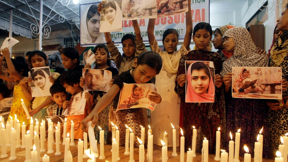 A Pakistani girl lights a candle as others hold pictures of 15-year-old Malala Yousufzai while they take part in a candlelight vigil in Karachi, Pakistan, Saturday, Nov. 10, 2012. (AP / Fareed Khan)