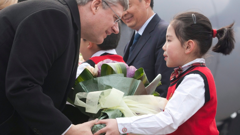 Prime Minister Stephen Harper is presented with flowers as he arrives in Chongqing, Saturday, Feb.11, 2012. (Adrian Wyld / THE CANADIAN PRESS)